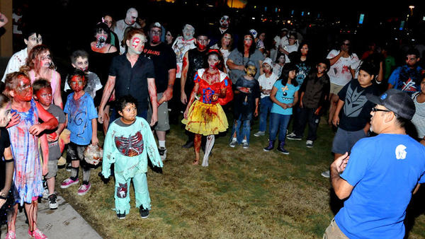 People dressed as zombies get into character Sunday during the Zombie Walk at Cinemark at the Imperial Valley Mall in El Centro.