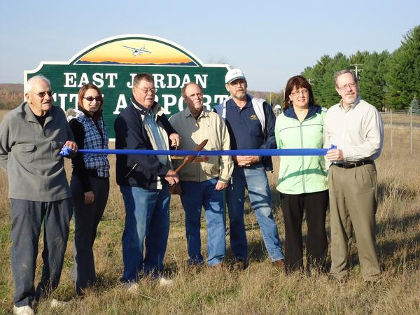 East Jordan community leaders and volunteers gathered to celebrate a ribbon cutting for the north/south runway at the East Jordan Airport last Wednesday. Pictured are (left to Right) volunteer Bob Strehl, East Jordan Chamber Ambassador Courtney Fender, Airport Assistant Manager Tom Sheridan, East Jordan Chamber of Commerce Board Member Frank Leonard, volunteer Terry Graham, East Jordan Chamber of Commerce Executive Director Mary Faculak and East Jordan City Administrator Chris Yonker.