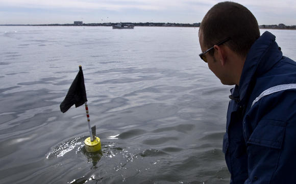 Va Marine Police Officer Shawn Hixenbaugh checks a gill net buoy