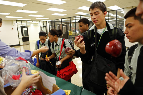"Students at Carver Military Academy in Chicago accept apples after signing a ""Pledge to Be Orange Finger Free,"" giving up Flamin' Hot Cheetos, Takis and other hot chips. Some of the kids pledged not to have them for a day and others gave them up for the rest of the school year."