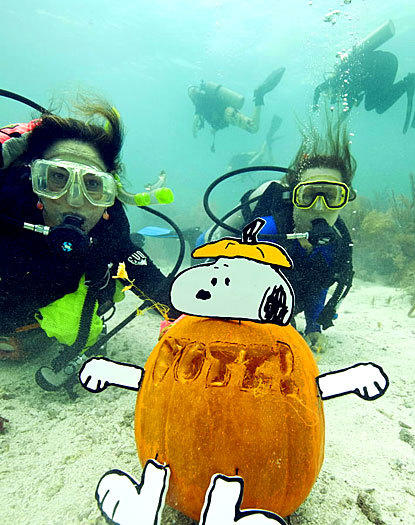"Divers Jana Vandelaar and her daughter show off their Snoopy jack-o-lantern with a ""Vote"" message at the Underwater Pumpkin Carving Contest in Key Largo, Fla."