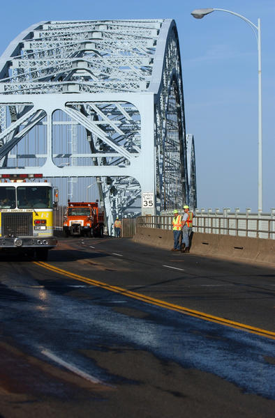 Connecticut Department of Transportation workers clean the Portland Bridge after two cars and four motorcycles collided