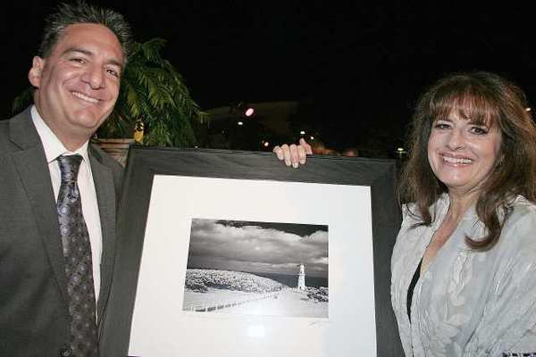 Glendale Community College Board of Trustees member and photographer Vahe Peroomian holds one of his donated photographs with Foundation Executive Lisa Brooks.