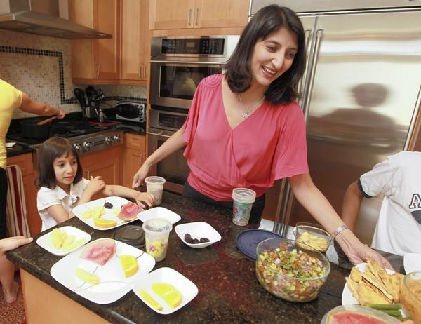 Ruchi Gupta, a pediatrician who's partnering with Chicago Public Schools to improve the management of food allergies, prepares a snack with her daughter, 5, who is allergic to peanuts and tree nuts.