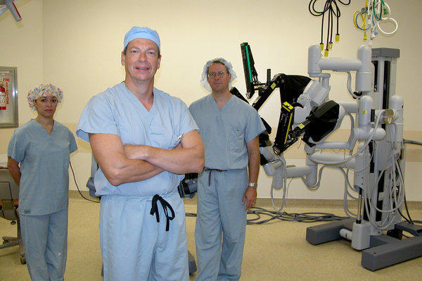 Dr. Timothy Wilson (center), head of the urology department at City of Hope, stands with a da Vinci surgical robot