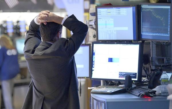 A trader works on the floor of the New York Stock Exchange as the Dow Jones industrial average plummeted more than 200 points.