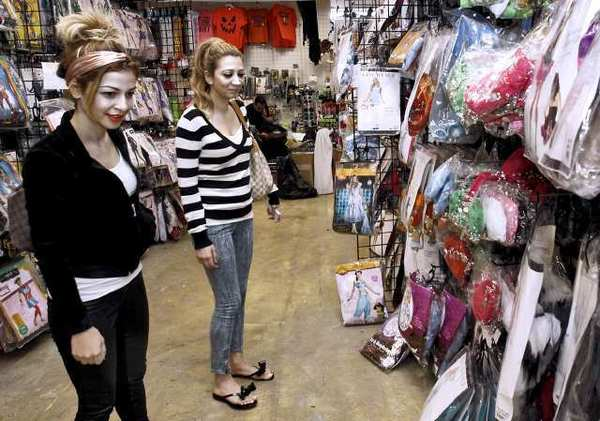Lara Kay, left, and Gina Dermamjian, right, both 23 and from Burbank, look for Halloween costumes at Halloween Superstore on Brand Boulevard in Glendale on Tuesday.