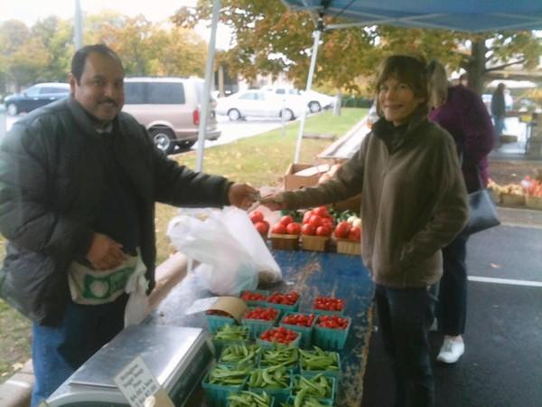 Agustin Alvarez,of Kap Farms sells vegetables to Laura Heissel of Arlington Heights.