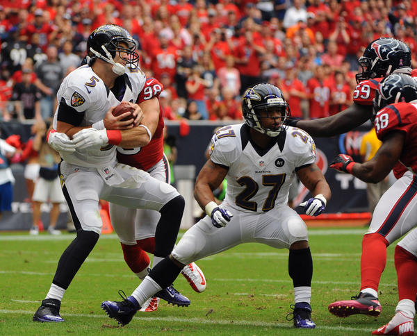 Ravens quarterback Joe Flacco (5) is sacked by the Houston Texans' Connor Barwin in the end zone for a safety in the first quarter at Reliant Stadium. Ravens running back Ray Rice (27) is occupied trying to block other pass rushers.