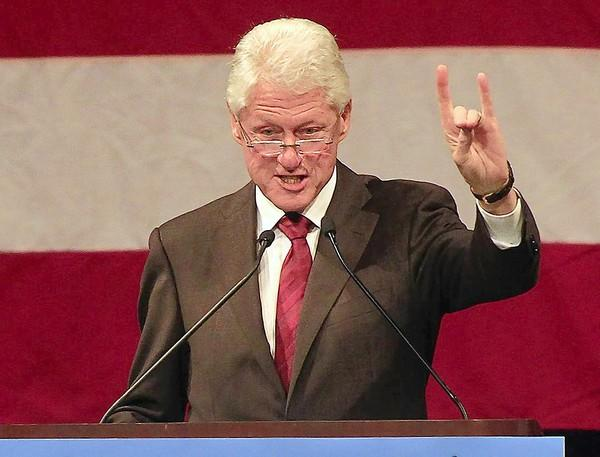 Former President Clinton makes the sign of the anteater, the UC Irvine mascot, during a campaign rally on the campus for five Democratic congressional candidates.