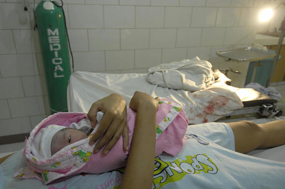 A new born baby girl lays atop her mother moments after her delivery inside a maternity clinic.