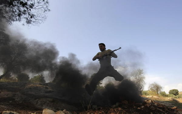 A Free Syrian Army (FSA) fighter jumps over a fire during a training session at an FSA camp in the countryside of Idlib.