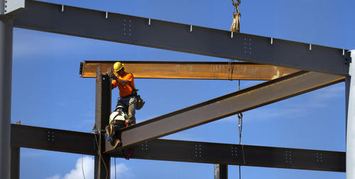 Steel workers attach a beam to a structure along Washington Ave. Wednesday as work in the new Apprentice school complex continues.