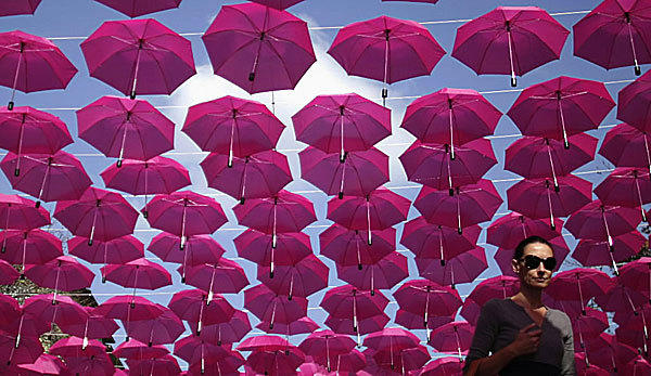A woman traipse under a canopy of pink umbrellas in Sofia, Bulgaria. The display, which has more than three hundred umbrellas, is part of the Breast Cancer Awareness campaign for the month of October.
