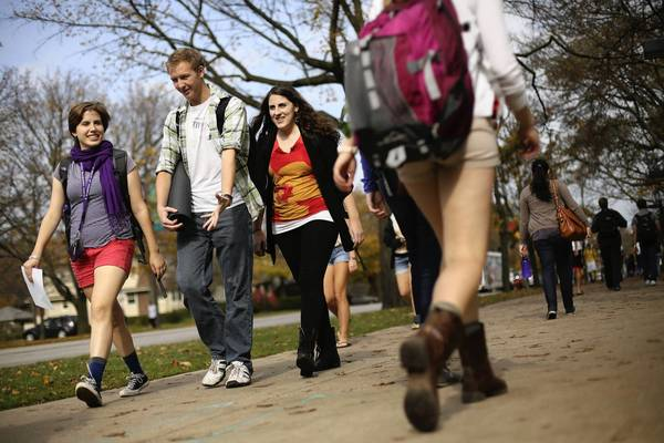 Students, some dressed for the warm weather, walk to class on the Northwestern University campus.