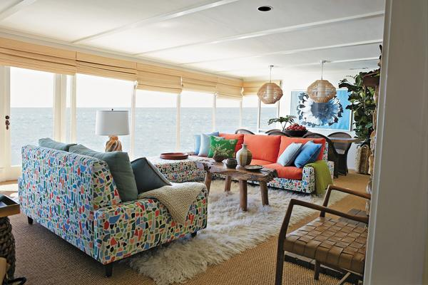 "Nathan Turner divides his book into three California living styles: beach, city and country. In his take on a mid-century beach house, the base of the seating is upholstered in a fabric by Lulu DK, and the cushions are in complementary solids. ""Let's face it,"" Turner writes, ""the pattern is busy. If I made the entire sofa in that print, I would have had one of those Gloria Vanderbilt-type situations where I do the walls and curtains and then a jumpsuit all in the same crazy pattern."" To balance all that color, he chose a neutral backdrop: seagrass on the floor with a Flokati rug, and budget-friendly matchstick blinds from blinds.com. In the dining area, he used a plain table surrounded by simple wicker chairs from Pottery Barn."