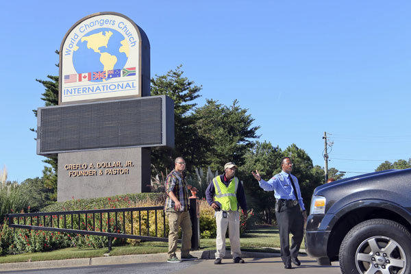 Security personnel stop cars coming onto the campus of World Changers Church International in College Park, Ga.