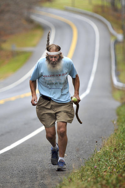 "NORFOLK Stephen Place, 72, of Lakeville, Massachusetts, jogs up Rt. 44 in Norfolk during his cross-country trek he's calling ""Jogging for Jesus.""  Place, a Pentecostal Christian, plans to take four to six months to jog to San Diego, California.  ""I'm trying to start a fire across this country,"" he explained, and was compelled to undertake the run to raise awareness about the teachings of Jesus Christ. Place took care of his wife of 54 years during a 10-year illness, and gained about 80 pounds.  He suffered a heart attack in 2003 and had a near-death experience.  After his wife passed away, Place starting jogging to take off the weight, and eventually felt fit enough to undertake the run.  He averages 15 miles per day, but would like to work up to covering 26 miles per day in the weeks to come as he makes his way across the country.  His grandson is following along in an RV to provide support and lodging."