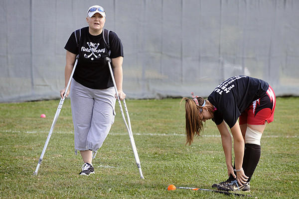 North Carroll field hockey assistant coach Laura Heinle, 43, left, was diagnosed with bone cancer in May. She is pictured as senior Gina Tolomei, right, stretches before practice.