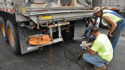 State Department of Transportation equipment operators Chris Kapitan Jr. and Nelson Saylor connect a spreader hose to the auger supply on one of the trucks used during winter snow removal.