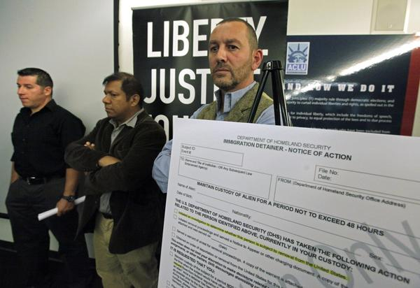 Lead plaintiff Duncan Roy, right, appears at a news conference to announce a federal lawsuit by the American Civil Liberties Union on behalf of arrestees who say they were denied bail because they had federal immigration holds, in Los Angeles.