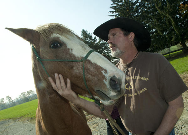 Warnshuis of Redding (right), California, pets Sandy, an 8-year-old mustang he is riding across the US, during a day long break from at Willowbrook Farm outside Catasauqua on Wednesday. Warnshuis began a cross-country trip to raise to raise awareness for Guillain-Barre syndrome on March 28, 2011, and is headed to New York City, where he will end his journey in Times Square. There, he will culminate the trip by getting married. Tuesday night. He arrived at Willow Brook, Tuesday night, where he stayed with his horses.