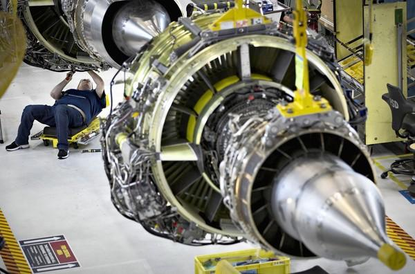 A worker in Renton, Wash., builds an engine for a Boeing 737-900. Chicago-based Boeing on Wednesday announced higher-than-expected profits in the third quarter, raised its earnings forecast for the year and provided an optimistic outlook for commercial airplane sales.