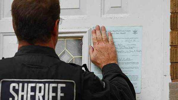 A Cook County sheriff's deputy puts a foreclosure notice on the door of a Chicago home.