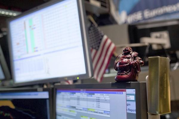 "A statue of the Buddha sits on top of a trading terminal on the floor of the New York Stock Exchange. One author says you can eliminate negative thinking and develop a ""Buddha brain"" by following a few simple steps."