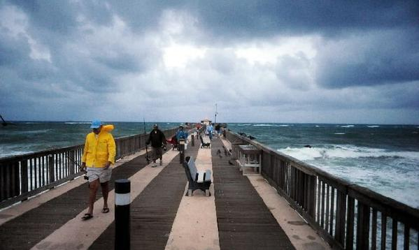 Fishermen leave the Pompano Beach Pier, Thursday, Oct. 25, 2012, after it was closed due to high winds and waves kicked up from  Hurricane Sandy.