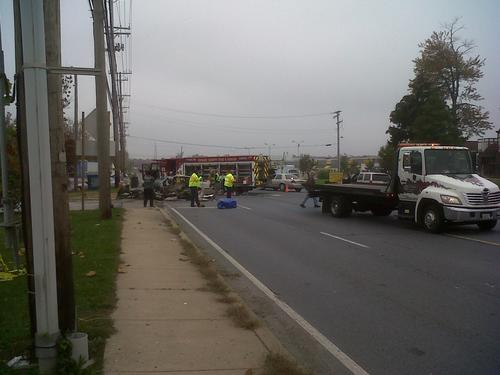 Rescue workers tend to the scene of a car crash on Route 1 in Elkridge Thursday, Oct. 25, in which three men traveling north on the road crashed into a tractor trailer. All three men died in the crash; the driver of the truck was uninjured.