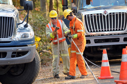 Two linemen with Hydro Quebec prepare a wire for installation on Lincoln Lane in Simsbury.