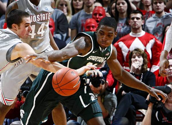 Ohio State Buckeyes guard Aaron Craft (4) tries to steal the ball from Michigan State Spartans guard Branden Dawson (22) during the second half at Value City Arena in Columbus, Ohio