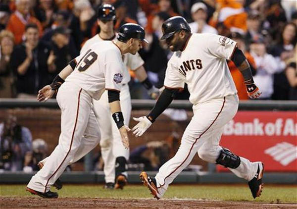 San Francisco Giants' Sandoval celebrates with teammate Scutaro after hitting a two RBI home run against the Detroit Tigers in the third inning during Game 1 of the MLB World Series baseball championship in San Francisco.