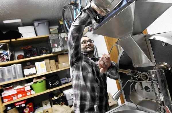 Will Cury, owner of Rogue Elephant Coffee Roasting Co., dumps coffee beans into his roaster. Cury and his wife, Renee, roast small batches of beans for local coffee shops and farmers markets.