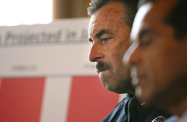 LAPD Chief Charlie Beck listens in April as Mayor Antonio Villaraigosa unveils a budget plan at City Hall.