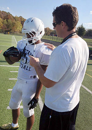 Meade football coach Rich Holzer talks with Mustangs wide receiver Daivon Nixon, left.
