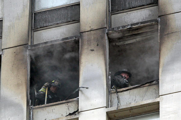 Chicago Fire Department firefighters get a breath of fresh air while extinguishing a fire on the 24th floor of a high rise building at 2626 N.Lakeview.