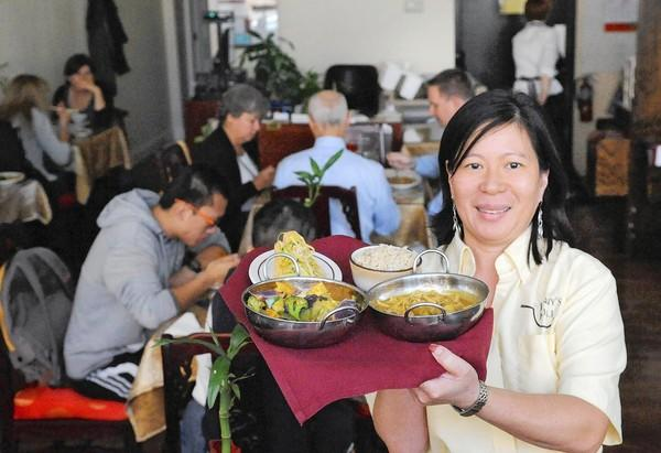 Jenny Lim, owner of Jenny's Kuali in south Bethlehem, holds a tray of Satay Tofu appetizer, a bowl of brown rice, and entrees Malaysian Curry Vegetables, and Malaysian Curry Chicken.