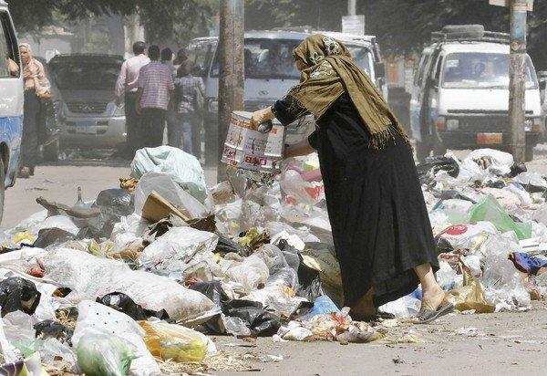 "A woman throws away garbage in Cairo. ""The trash keeps increasing,"" one street sweeper said. ""It's the only thing in Egypt we don't run out of."""