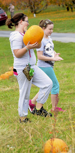 Haylee Watson, left, and Lily Erwin walk out of the pumpkin patch at Lewis Orchids in Smithsburg with their selection.