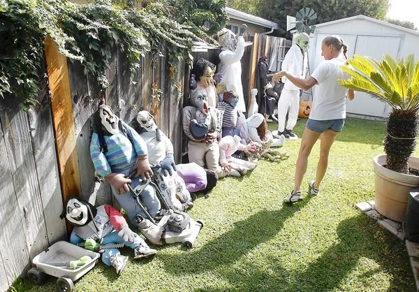 "Colleen Hanson points out a wall of characters used in her family's annual ""Halloween House"" display that lights up the neighborhood in Eastside Costa Mesa, 276 E. Wilson St."