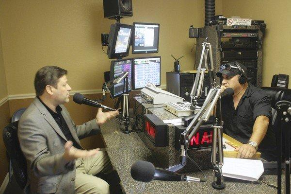 Radio host Fernando Miguel Negron, right, debates politics with Orlando lawyer Jim Jimenez, who is appearing on a segment of the Florida talk show bought by Mitt Romney's presidential campaign.