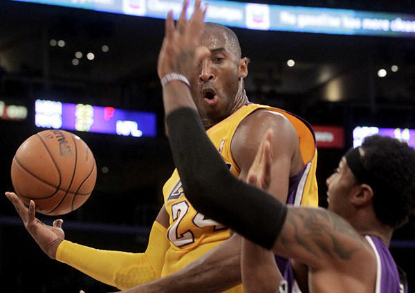 Lakers guard Kobe Bryant flips a no-look pass as his drive is cut off by Kings guard James Johnson in a preseason game Sunday.
