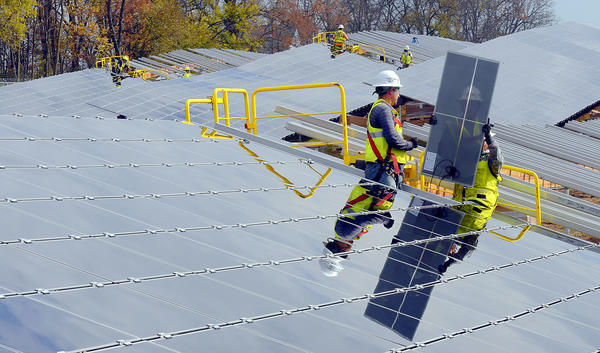 Jose Garcia, left, and Santiago Anaya, install thin film solar panels along Roxbury Rd. south of Hagerstown on Wednesday. Approximately 332,100 panels will be in place and each panel will produce 87.5 watts.