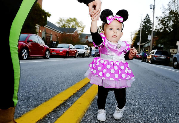 Kierra Saunders, 1, dressed as Minnie Mouse is led down the parade route in Funkstown by her mother Thursday evening for the annual Funkstown Halloween Parade.