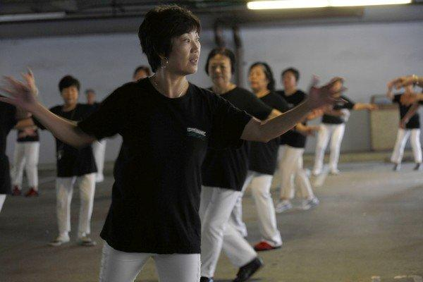 Kit Cheung leads members of the Dynamic Line Dance group, which meets in a parking garage at the Monterey Park library.