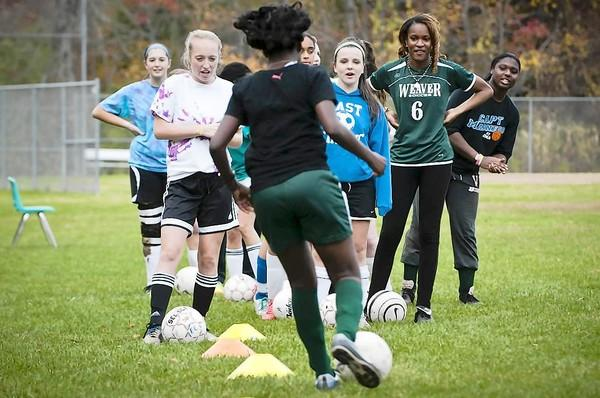 Members of the East Catholic Girls' Varsity Soccer team and the Weaver High Girls Varsity drill during a joint practice aimed at fostering cultural relations and good sportsmanship.