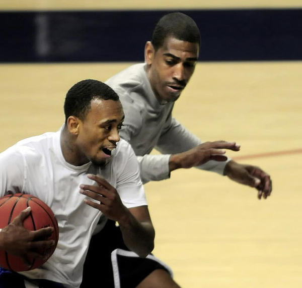 UConn coach Kevin Ollie, right, here working with Ryan Boatright, is out to increase the Huskies' point production this season.