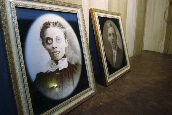 Portraits in a bedroom of a haunted house built Preston Meyer, of Burbank, that he built in his front yard in Burbank on Friday, October 26, 2012.